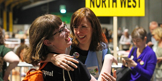 """People from the""""Yes"""" campaign react as the results of the votes begin to come in, after the Irish referendum on the 8th Amendment of the Irish Constitution at the RDS count centre, in Dublin, Ireland, Saturday ."""