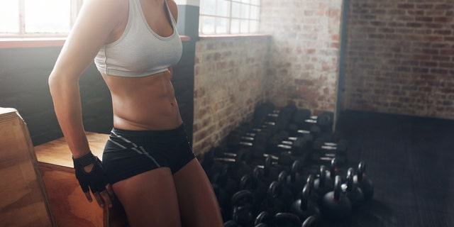Indoor shot of a fit woman taking a break from her workout at a gym. Fitness instructor relaxing at a gym.