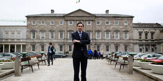 Ireland's Minister of State for Finance Simon Harris poses for a picture in front of Leinster House in Dublin, March 2015.