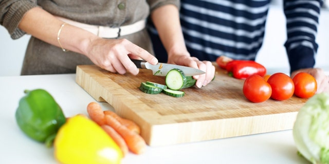 Cropped image of a couple preparing a salad, slicing cucumber on a wooden chopping board