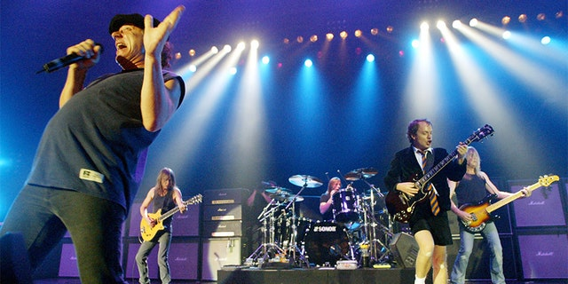 Rock band AC/DC, from left, Brian Johnson, Malcolm Young, Phil Rudd, Angus Young, and Cliff Williams performing on stage during a concert in German in 2003.