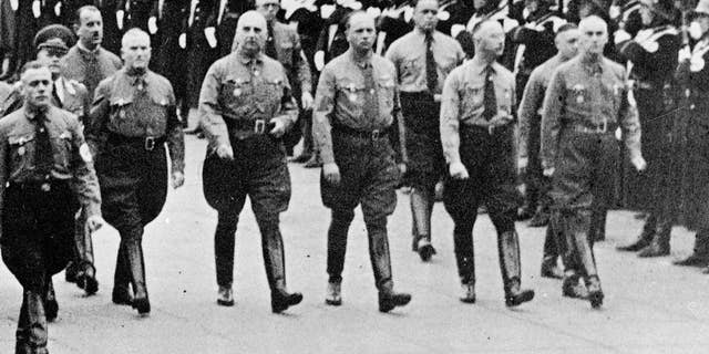 FILE - In this 1938 file photo Heinrich Himmler, second right, chief of secret police and Dr. Wilhelm Frick, right, and other leading members of the Nazi party march along Koenigliche Platz in Munich, southern Germany. A historical commission examining the Nazi links of Germany's Interior Ministry says more than half of the staffers from 1949 to 1970 had belonged to the Nazi party. In an interim report presented Wednesday, Nov. 4, 2015 the commission said 54 percent of staffers during those years had been former Nazi party members, and many had also been members of the SS or SA. Eight percent had served in the Nazi Interior Ministry, which was run by Wilhelm Frick, who was executed for war crimes, and later SS-chief Heinrich Himmler.  (AP Photo/file)