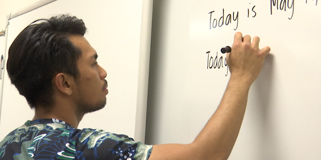 Adrian Calabano, 23, readies his classroom. Filipino and here on a J-1 visa, he teaches sixth grade special education at a junior high school outside Las Vegas.