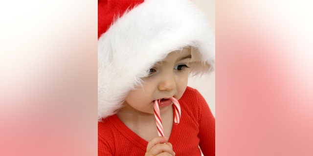 Adorabel toddler boy eating a candy cane wearing a santa hat and red long-johns.