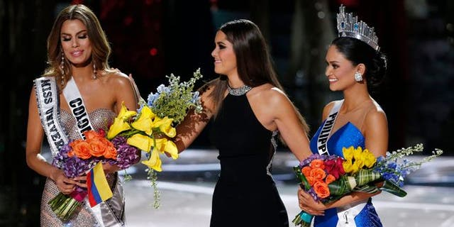 Former Miss Universe Paulina Vega, sentrum, takes away the flowers and sash from Miss Colombia Ariadna Gutierrez, links, before giving them to Miss Philippines Pia Alonzo Wurtzbach, reg, by die 2015 Miss Universe pageant.