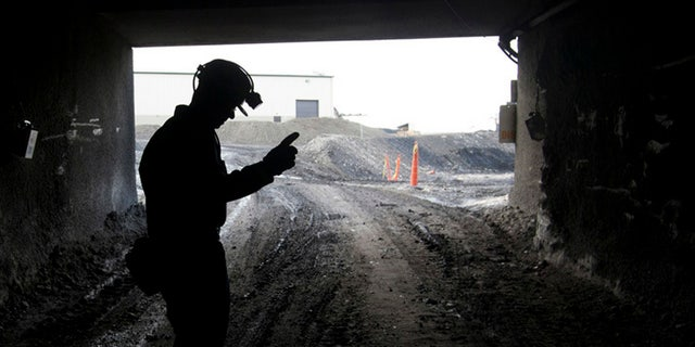 In this Nov. 9, 2010 file photo, a mine employee stands in the entry of the Signal Peak Energy's Bull Mountain mine in Roundup, Montana.