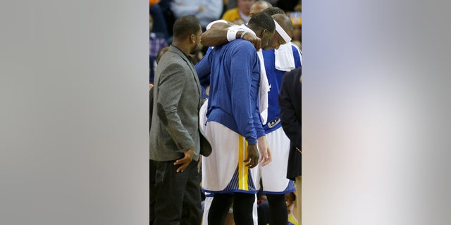 Golden State Warriors center Jermaine O'Neal, right, is helped off the floor after being injured during the fourth quarter of an NBA basketball game against the Utah Jazz in Oakland, Calif., Saturday, Nov. 16, 2013. The Warriors won 102-88. (AP Photo/Jeff Chiu)