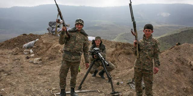 Armenian soldiers pose near a front line in Nagorno-Karabakh, Azerbaijan, Wednesday, April 6, 2016. (Karo Sahakyan/PAN Photo via AP)
