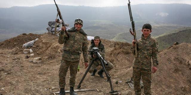Armenian soldiers pose near a front line in Nagorno-Karabakh, Azerbaijan, Wednesday, April 6, 2016. (Karo Sahakyan/PAN Photo via AP)
