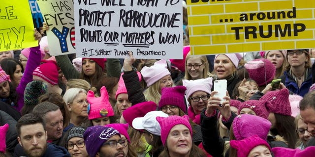 """January 21, 2017: Women with bright pink hats known as the """"pussy hats"""" gather for the Women's March in Washington, DC."""