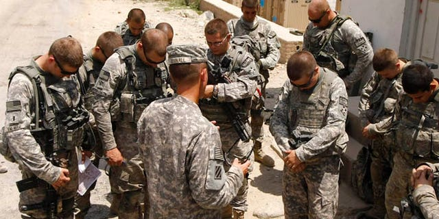Chaplain Wes Gornall (C) prays with members of Alpha Company, 2-12 Infantry, 4th Brigade of NATO's International Security Assistance Force (ISAF) before boarding a helicopter at Forward Operating Base Blessing in Kunar Province, to support Chosen Company in the Watapor Valley July 17, 2009. REUTERS/Tim Wimborne    (AFGHANISTAN CONFLICT) - RTR25R8E