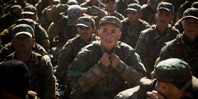 Nov. 26, 2013: An Afghan army soldier adjusts his uniform during an outdoor lesson at a training facility in the outskirts of Kabul, Afghanistan.
