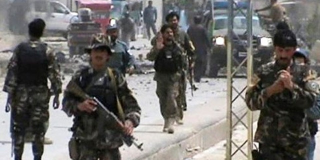 April 6, 2013: This image shows Afghan National Army soldiers rushing to the scene moments after a car bomb exploded in front the PRT, Provincial Reconstruction Team, in Qalat, Zabul province, southern Afghanistan.
