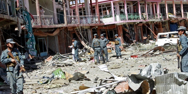 Sept. 4, 2014: Afghan security forces walk at the site of a suicide attack in Ghazni, Afghanistan. The Taliban struck a government compound in eastern Afghanistan early on Thursday in an attack that included two suicide truck bombings and left nearly a dozen dead, including several off duty policemen asleep in their quarters nearby, officials said.