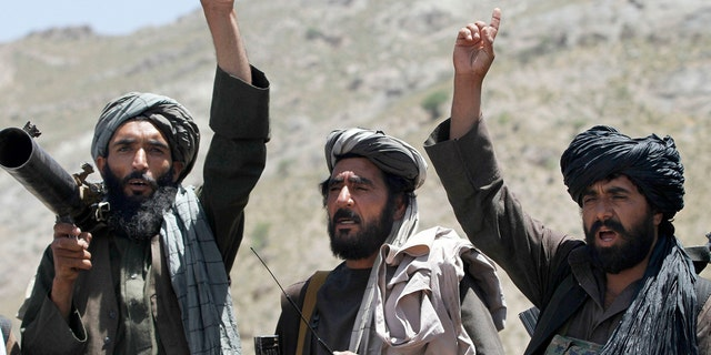 In this May 27, 2016 file photo, Taliban fighters react to a speech by their senior leader in the Shindand district of Herat province, Afghanistan.