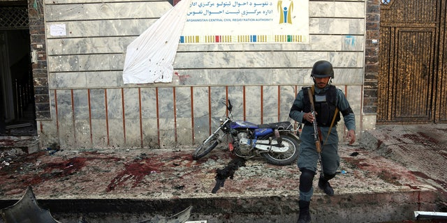 An Afghan police walks outside a voter registration center which was attacked by a suicide bomber in Kabul, Afghanistan, Sunday, April 22, 2018.