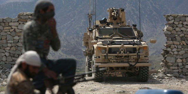 FILE - In this April 17, 2017, file photo, U.S. forces and Afghan security police are seen in Asad Khil near the site of a U.S. bombing in the Achin district of Jalalabad, east of Kabul, Afghanistan. The Pentagon will send almost 4,000 additional American forces to Afghanistan, a Trump administration official said June 15, hoping to break a stalemate in a war that has now passed to a third U.S. commander-in-chief. The deployment will be the largest of American manpower under Donald Trump's young presidency. (AP Photo/Rahmat Gul, File)