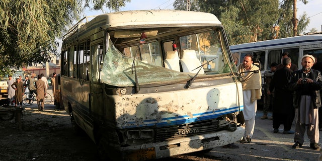 People look at a damaged bus after a suicide attack in Jalalabad city, Afghanistan November 23, 2017