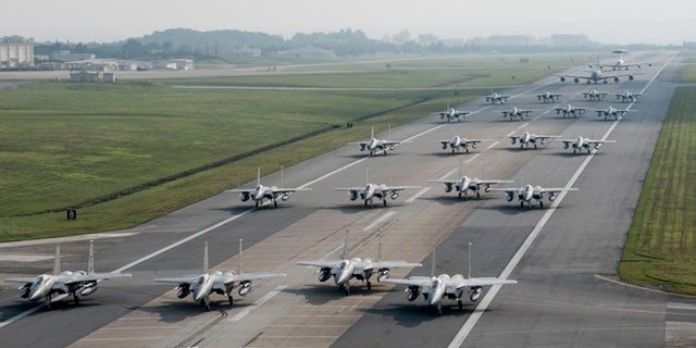 U.S. Air Force 44th and 67th Fighter Squadron F-15 Eagles and 961st Airborne Air Control Squadron E-3 Sentries taxi down the runway.
