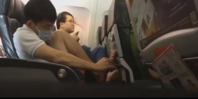 The unidentified man proceeded to pick dried skin from his feet and drop it onto the plane floor.