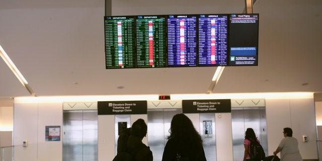 Airline passengers look at a flight status board at San Francisco International Airport in San Francisco