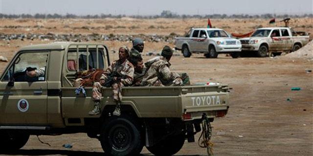 Libyan rebel fighters patrol along the western gate of Ajdabiya, Libya, April 23.