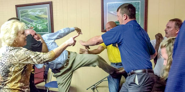 Alexander City, Ala Mayor Charles Shaw, left, is restrained by an officer after a fight broke out between him and councilman Tony Goss, far right, during a meeting of the Alexander City City Council in Alexander City, Ala. on Monday, April 25, 2016.