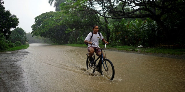A man rides a bicycle down a flooded road as Subtropical Storm Alberto passes by the west coast of Cuba, in Bahia Honda, Cuba, May 26, 2018.