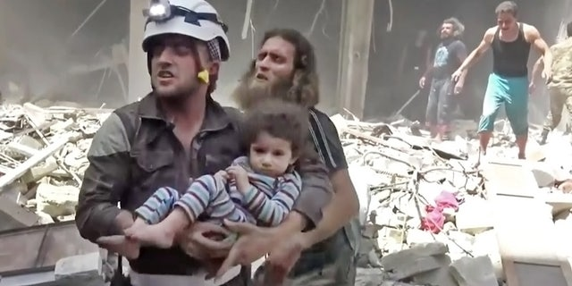 April 28, 2016: In this image made from video and posted online from Validated UGC, a Civil Defense worker carries a child after airstrikes hit Aleppo, Syria.