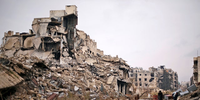 December 17, 2016: People carry belongings as they walk on the rubble of damaged buildings in the government controlled area of Aleppo, Syria.