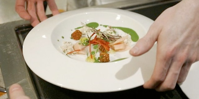 Chef Grant Achatz places a dish on a server's tray at Alinea in Chicago.