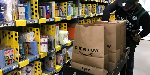 FILE PHOTO: An employee collects items ordered by Amazon.com customers through the company's two-hour delivery service Prime Now in a warehouse in San Francisco, California, U.S., December 20, 2017. REUTERS/Jeffrey Dastin