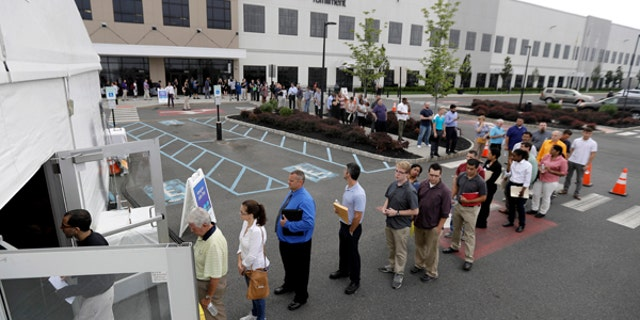 Job candidates stand in line outside a processing tent set up at an Amazon fulfillment center in Robbinsville, New Jersey, during Wednesday's job fair.