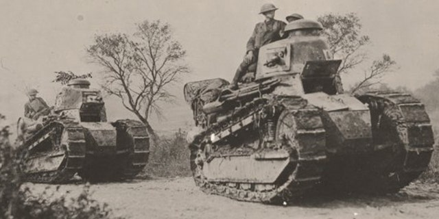 American soldiers, near Boureuilles, ride on top of tanks on the way to a division's headquarters on the first day of the Meuse-Argonne Offensive.