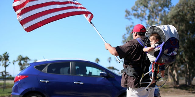 Demonstrator Steven Morales with his son Steven Jr. waves an American flag for motorists in support of President elect Donald Trump outside of Camp Pendleton in Oceanside, California, U.S. November 11, 2016.  REUTERS/Sandy Huffaker - RTX2TA95