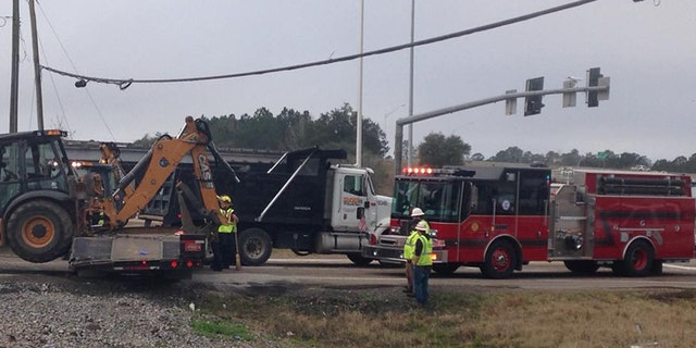 Authorities respond after an Amtrak train struck a trailer carrying construction equipment in Slidell, La.