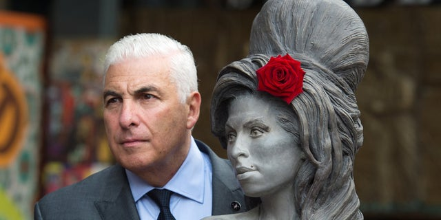 Winehouse's father with a statue of the singer in England.