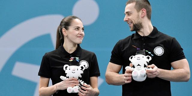 Bronze medalists Aleksandr Krushelnitskiy and Anastasia Bryzgalova, Olympic athletes from Russia, celebrate during the victory ceremony.