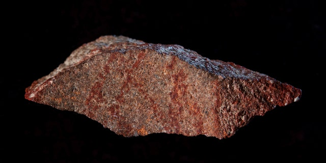 This undated photo provided by Craig Foster in September 2018 shows a drawing made with ochre pigment on silcrete stone, found in the Blombos Cave east of Cape Town, South Africa. In a report released on Wednesday, Sept. 12, 2018, scientists say this tiny 73,000-year-old sketch found in a South African cave is the oldest known drawing. (Craig Foster via AP)