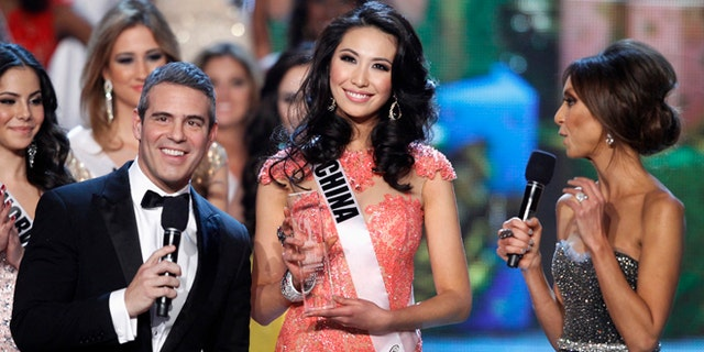 Miss China Xu Jidan poses with hosts Andy Cohen (L) and Giuliana Rancic after receiving the Best National Costume award during the Miss Universe pageant at Planet Hollywood Resort and Casino in Las Vegas, Nevada December 19, 2012. REUTERS/Steve Marcus (UNITED STATES - Tags: ENTERTAINMENT) FOR EDITORIAL USE ONLY. NOT FOR SALE FOR MARKETING OR ADVERTISING CAMPAIGNS - RTR3BRN2