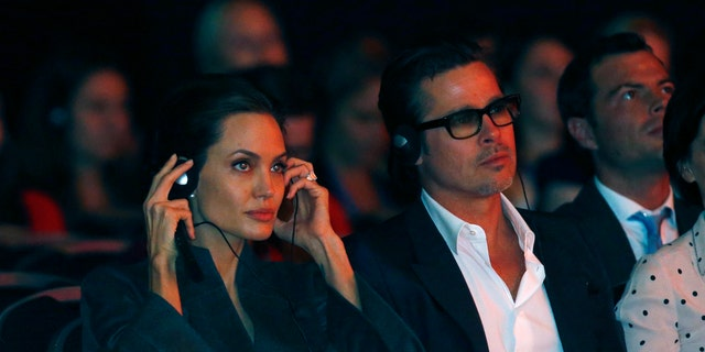 Actress and campaigner Angelina Jolie and her partner Brad Pitt wear headphones to listen to a translation during a global summit on ending sexual violence in conflict, at the ExCel Centre in London June 13, 2014. REUTERS/Luke MacGregor  (BRITAIN - Tags: POLITICS ENTERTAINMENT) - RTR3TMBJ