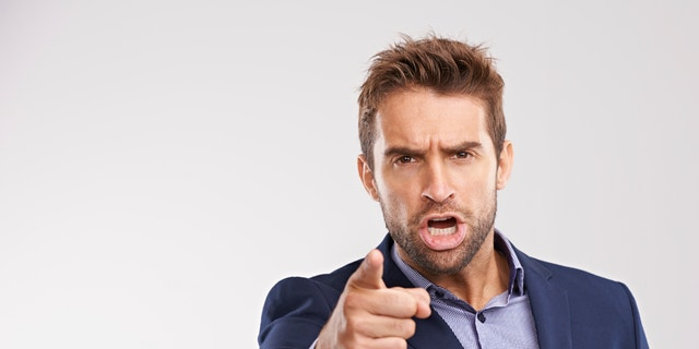 Portrait of an angry businessman pointing at the camera