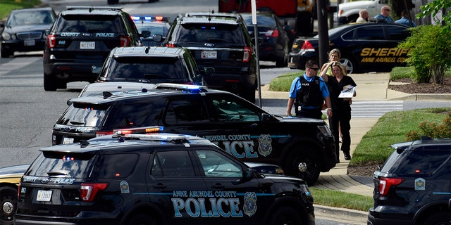 Police secure the scene of a shooting at the building housing The Capital Gazette newspaper in Annapolis, Md., on Thursday.