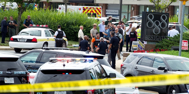 Authorities stage at the office building entrance after multiple people were shot at The Capital Gazette newspaper in Annapolis, Md., on Thursday.