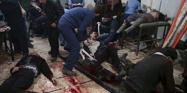 Medics treat injured people inside a field hospital after air and missile strikes in the Douma neighborhood of Damascus, Syria, in 2015. The injured are taken to basements and shelters transformed into field hospitals run by medical staff who have stayed in the battered neighborhood of Damascus.
