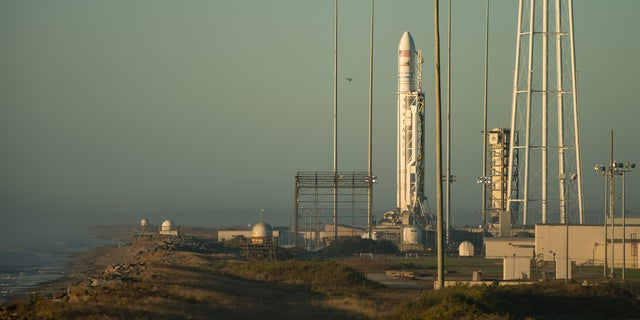 The Orbital ATK Antares rocket, with the Cygnus spacecraft onboard, stands tall on the launchpad as the sun rises behind it on Sunday (Oct. 16) at NASA's Wallops Flight Facility in Virginia.