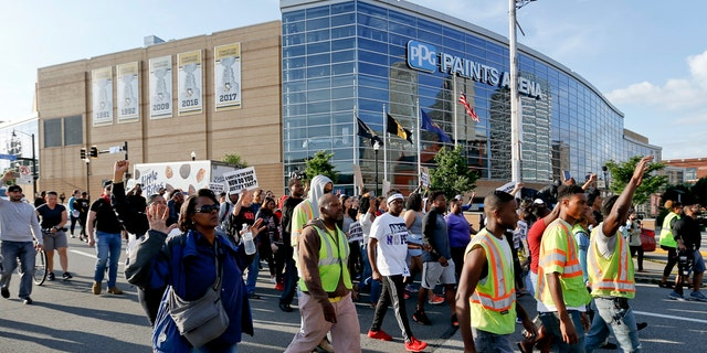 Marchers walk by PPG Paints arena as they protest the shooting death of Antwon Rose Jr. on Tuesday, June 26, 2018, in Pittsburgh