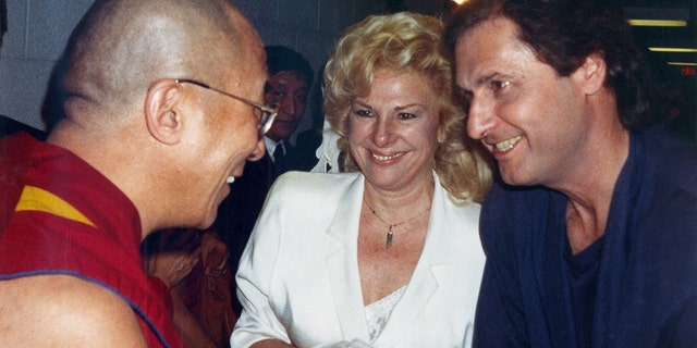 In this October 1989 file photo, the Dalai Lama, left, talks to the comedy writing and acting team of Renee Taylor and Joe Bologna, during a backstage visit prior to the Dalai Lama's convocation on the subject of compassion at UC Irvine in Irvine, Calif.