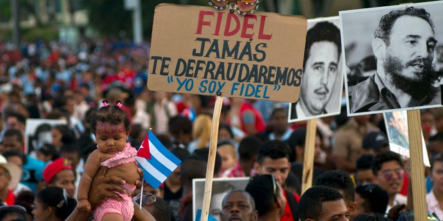 People wait at the beginning of a rally to honor Cuba's Fidel Castro in Santiago, Cuba, Dec. 3.