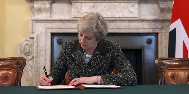 Britain's Prime Minister Theresa May signs the official letter to European Council President Donald Tusk, in 10 Downing Street, London, Tuesday March 28, 2017, invoking Article 50 of the bloc's key treaty, the formal start of exit negotiations. Britons voted in June to leave the bloc after four decades of membership. (Christopher Furlong/Pool Photo via AP)